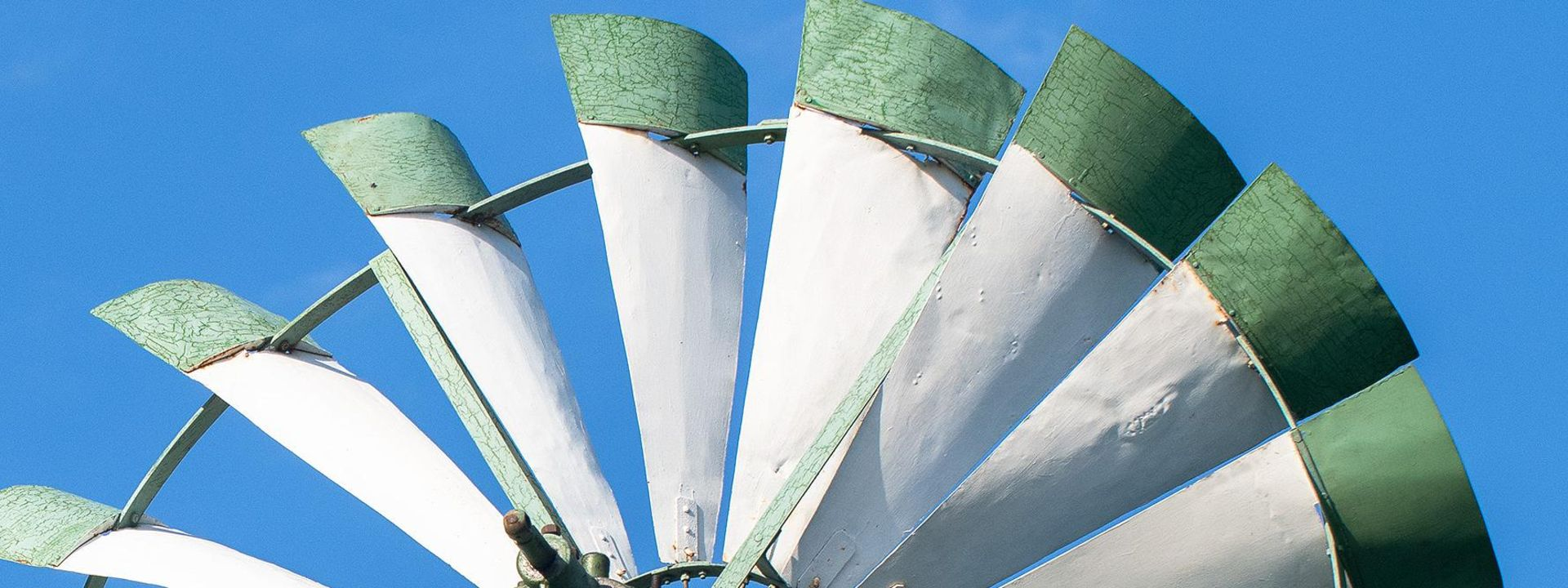 The white and green blades of a windmill against a blue sky.