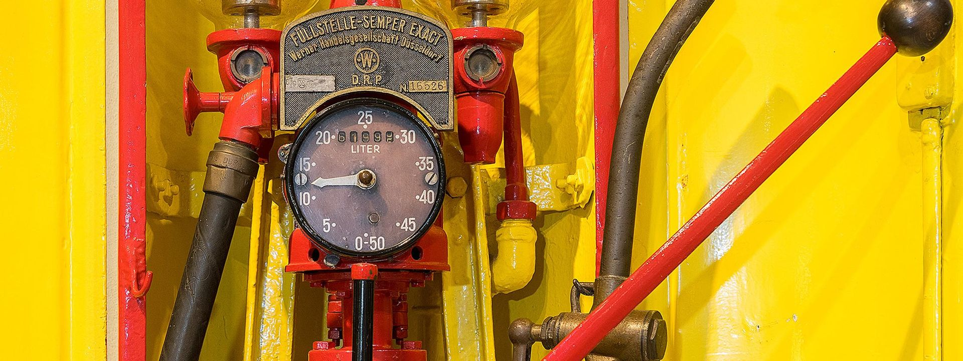 "A yellow and red fuel pump. The arrow on the analog gauge in the middle points to between ten and 15. On the metal plate above it, the words ""Füllstelle-Sempler Exact"" (""Precision Sempler Fuel Pump"") are written."