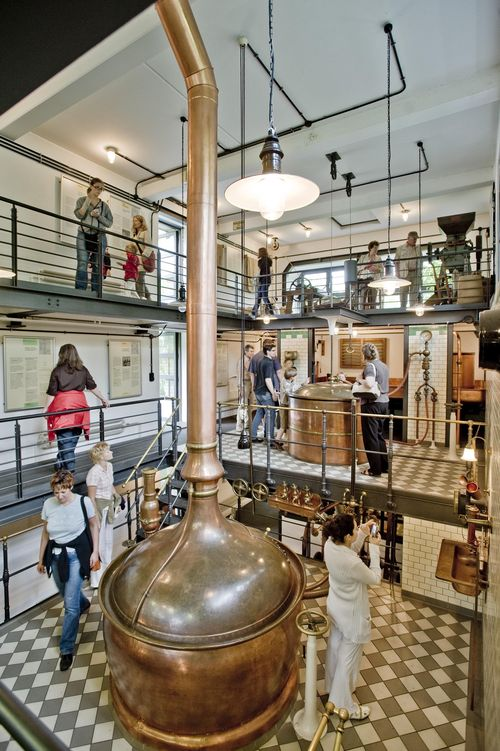 At the heart of the Historical Brewery is a large copper kettle with a massive pipe rising from the top. Museum visitors look at exhibits on the two half-floors arranged around the kettle and pipe.