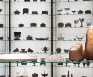 Household sugar in various forms: sugarloaves, crystallized rock candy, sugar pressed into rods. In the background, numerous sugar bowls made of silver can be seen.