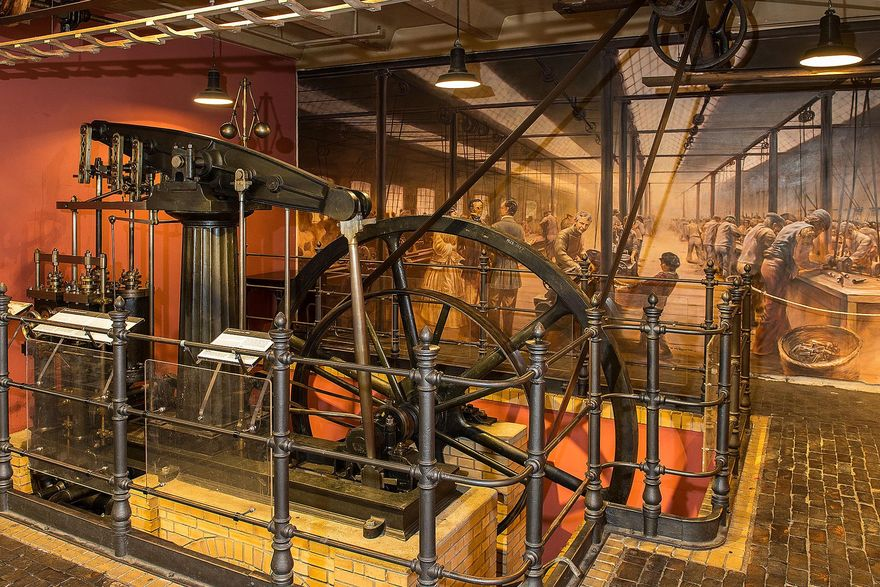 The central transmission shaft is enclosed by a railing. The smaller drive wheel with the transmission belt and the larger flywheel can be seen behind it. The pistons of the steam engine are in the foreground. In the background, there is a mural depicting a historical machine shop.