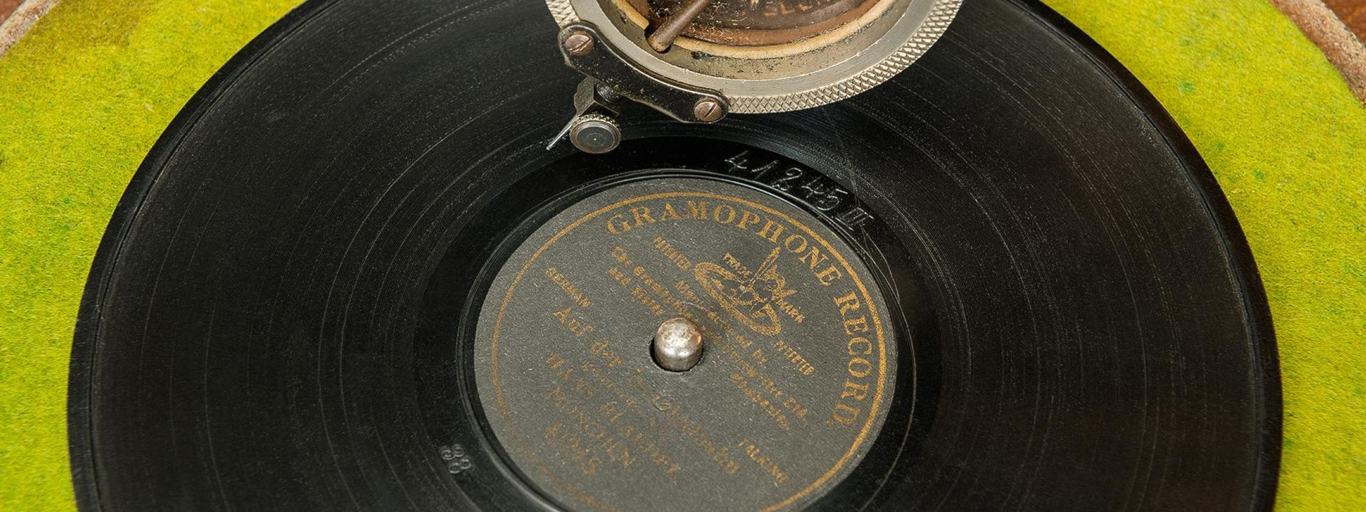 A record lies on green felt. A gramophone arm with a decorated sound box is positioned above it.