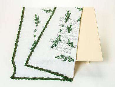 This rectangular tablecloth is made from white cotton. It is embroidered with green fir branches, which were applied by hand. An English language imprint on one part of the tablecloth is noteworthy. It shows that the tablecloth had previously been a flour sack.