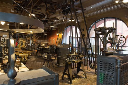 A view of the Historical Machine Shop, featuring several metalworking machines. Mounted to the ceiling are the line shaft and the various wheels and belts that transmit power from the steam engine to the machines.