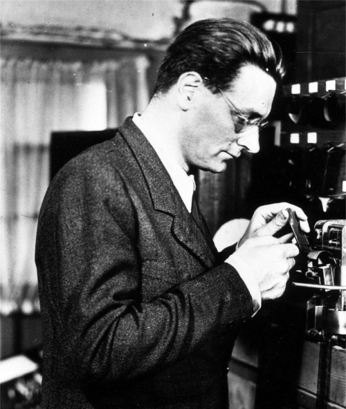 Black-and-white photograph: profile view of Konrad Zuse checking a punch tape.