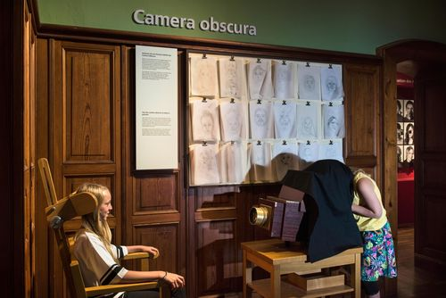 "View of a wood-paneled room in the exhibition. A young girl is bent over a large wooden camera, with a black cloth draped over her head. The camera is pointed at a girl sitting in an armchair. Simple, pencil-drawn portraits hang on the wall in the background. The words ""Camera obscura"" can be read above them."
