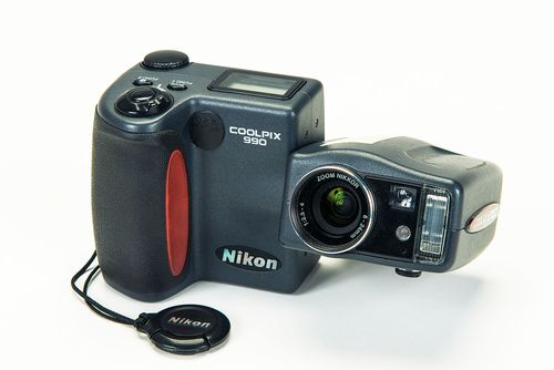 This digital camera consists of two parts, the screen and controls unit and the lens unit. The control unit has a handgrip for holding the camera. The shutter button, two function keys, a setting dial and a small digital display are located on its top face. The lens unit is connected to the control unit with a swivel hinge. It consists of the lens, the viewfinder, a light sensor and a small built-in flash.