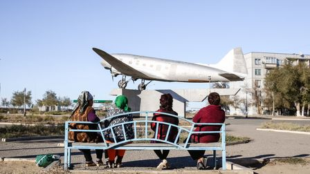 Four women are sitting on a park bench with their backs to the viewer. They are looking at a silver aircraft mounted on a concrete pedestal.