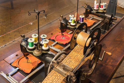 Overhead view of a large, historical embroidery machine. It has a punch card wound on a spool and three heads, each with thread of various colors and an embroidery frame.