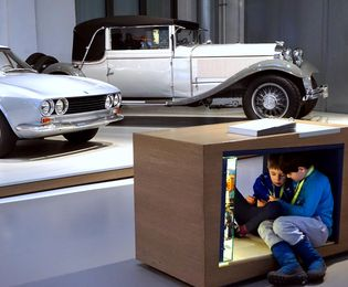 There are two children sitting in an open wooden cube. In front of them is a light box containing many small, colorful objects. In the background, there are two historical cars on a low platform.