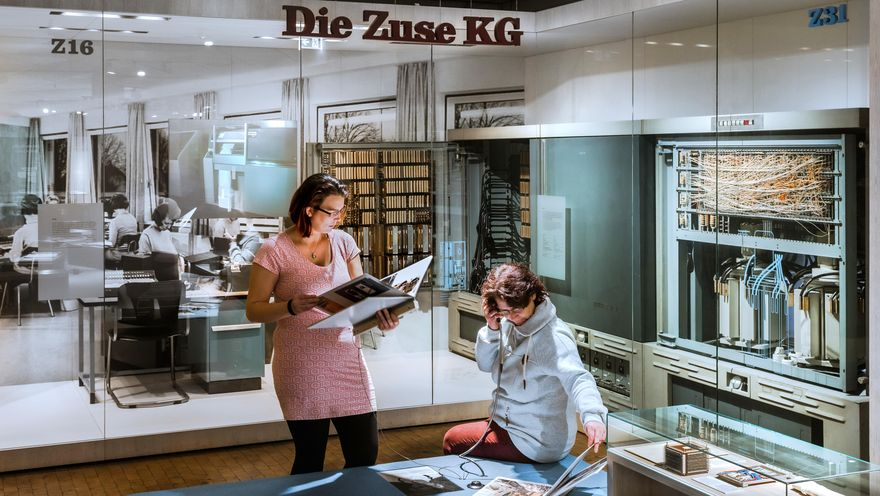 "A view of the Computers exhibition. A woman sits on a ledge at an audio station, holding a handset to her ear. Another woman stands next to her, reading a large brochure. In the background, tall display cases containing historical computers can be seen. The words ""Die Zuse KG"" (The Zuse KG Company) hang from the ceiling."