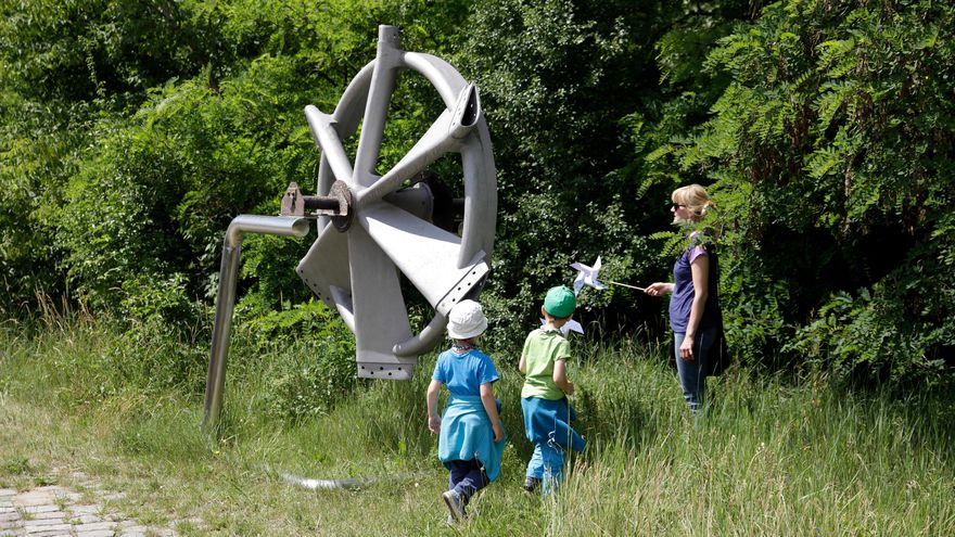 Two children and a woman look at a windmill hub. It is fastened to a metal support standing in high grass.