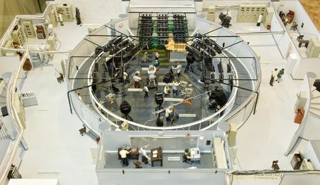 A circular television studio divided into two levels. The studio, including a stage, is below. The control room is above.