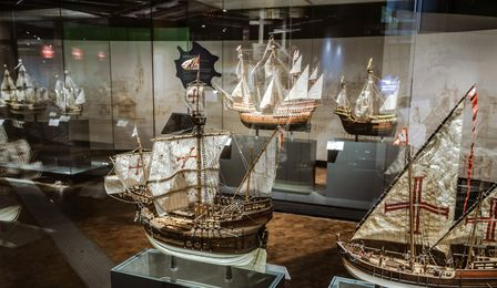 A line of display cases containing various models of sailing vessels.
