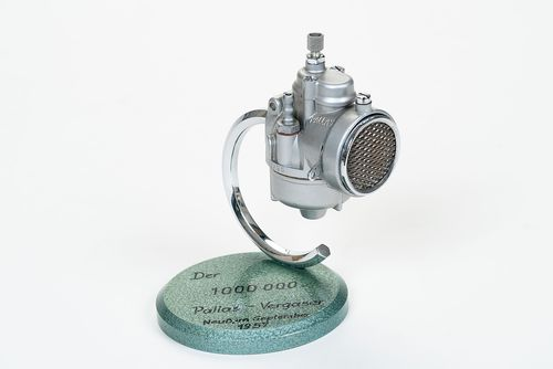 The millionth Pallas carburetor is mounted on a round pedestal. It is a carburetor for a small moped. The pedestal has a green hammer paint finish upon which the jubilee and the date are noted in black lettering.