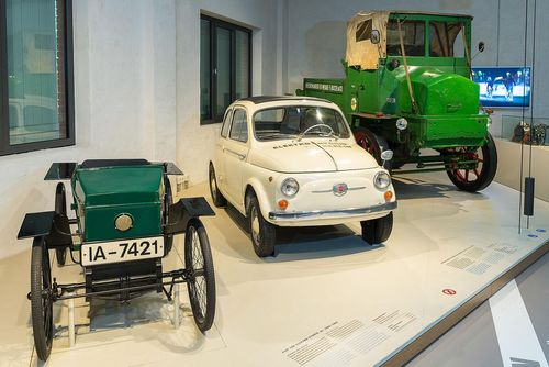 There are three historical electric cars on a low platform. From left to right: a green open-topped car (similar to a soapbox car), a white Fiat 500, and a green flatbed truck.
