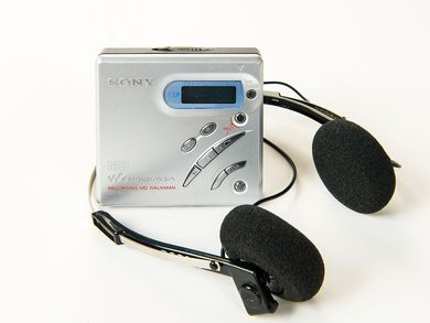 This MZ-R500 MiniDisc Recorder has the shape of a small square box with asymmetrically arranged function keys and a silver colored aluminum surface.
