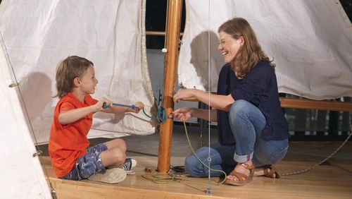 A woman and a young boy sit on opposite sides of a sailboat mast with raised sails. They are each holding a rope and tying knots.