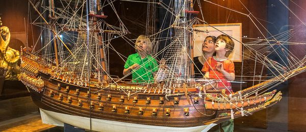 There are three children standing on a platform behind a display case, looking at a large, detailed model ship. A woman stands behind them.