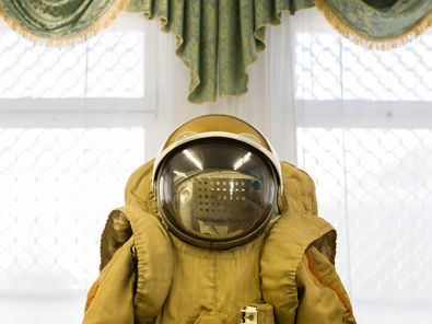 This image is a central view of a cosmonaut's suit from the waist upwards and includes a spherical helmet with a large glass visor. In the background, an ornamental hanging with a gold fringe is suspended above a window.