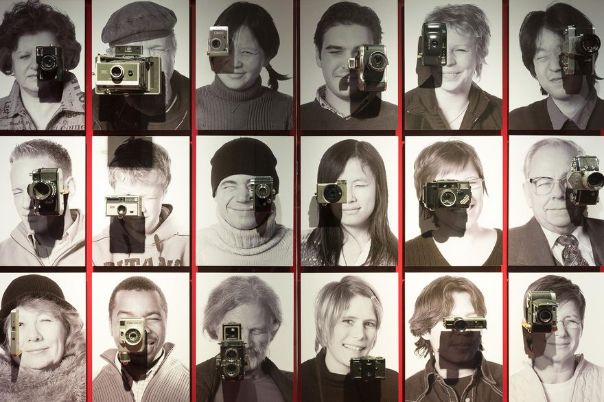 18 black-and-white portrait photos of men and women of various ages are arranged in three rows. In front of each face is a historical camera. The people look like they are taking pictures.