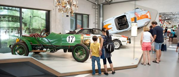A view of the Road Transport exhibition. There are several people standing in front of a low platform on which two historical racecars are displayed. Another blue and orange racecar is mounted on the wall. A ceiling installation made of numerous trophies hangs over the platform.