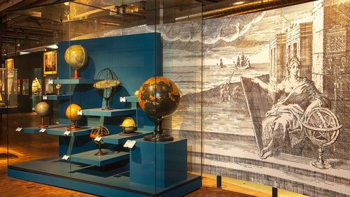 A display case with historical globes on blue stands. Behind it there is a large black-and-white image.