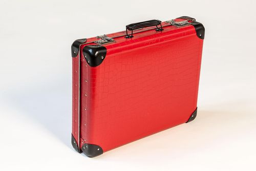 A closed, red hardboard suitcase with black corners and a black handle.
