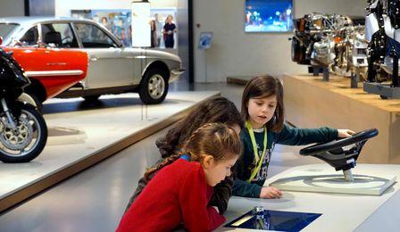 Two girls are bent over a media station in the exhibition. Next to them, another girl is looking at what they're doing. Her hand is resting on a steering wheel. In the background, cars and engines can be seen.