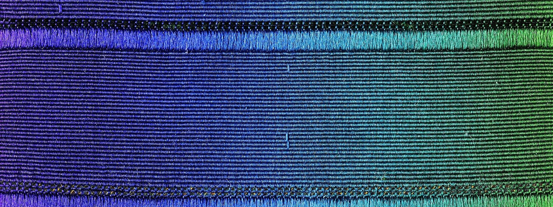 Close-up of a woven strap whose color fades from violet to blue to green.