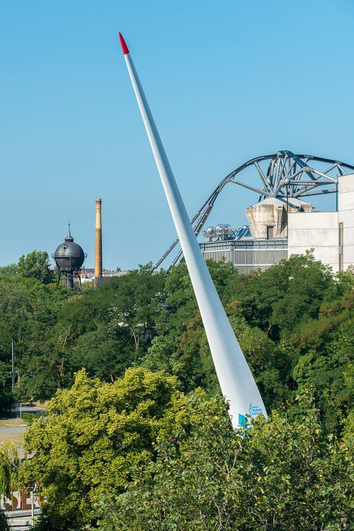 A large, white rotor blade rises vertically out of green treetops. In the background, the curved supporting girders of a roof structure, a water tower, and a chimney can be seen.