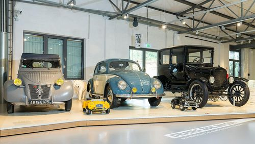 There are three cars on a low platform. From left to right: a gray Citroën 2CV, a blue and white VW Beetle, and an older black car.