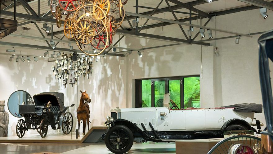 View of the Road Transport exhibition, featuring a historical white convertible, a horse and buggy, and a ceiling installation made of various wooden wheels.