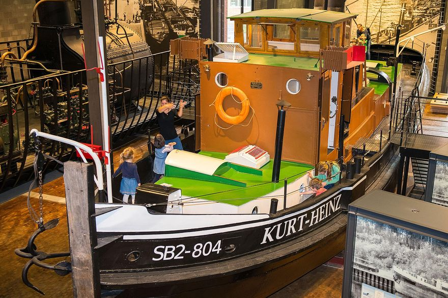 "A small, historical steamboat in the Shipping exhibition. There are several people standing on its foredeck. ""SB2-804"" and ""Kurt-Heinz"" are written on the side of the boat."
