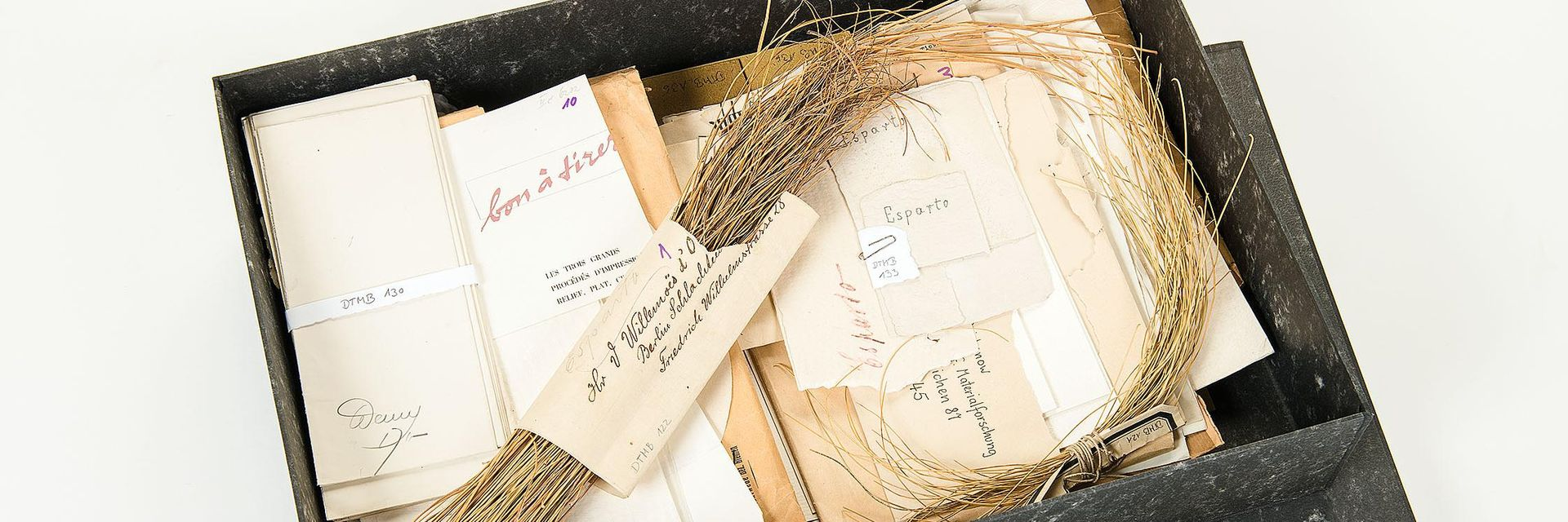 An open gray box with many envelopes and samples of various grass papers as well as dried grasses.