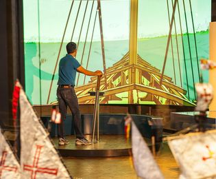 A man stands on a platform and steers a sailboat projected on the wall in front of him.