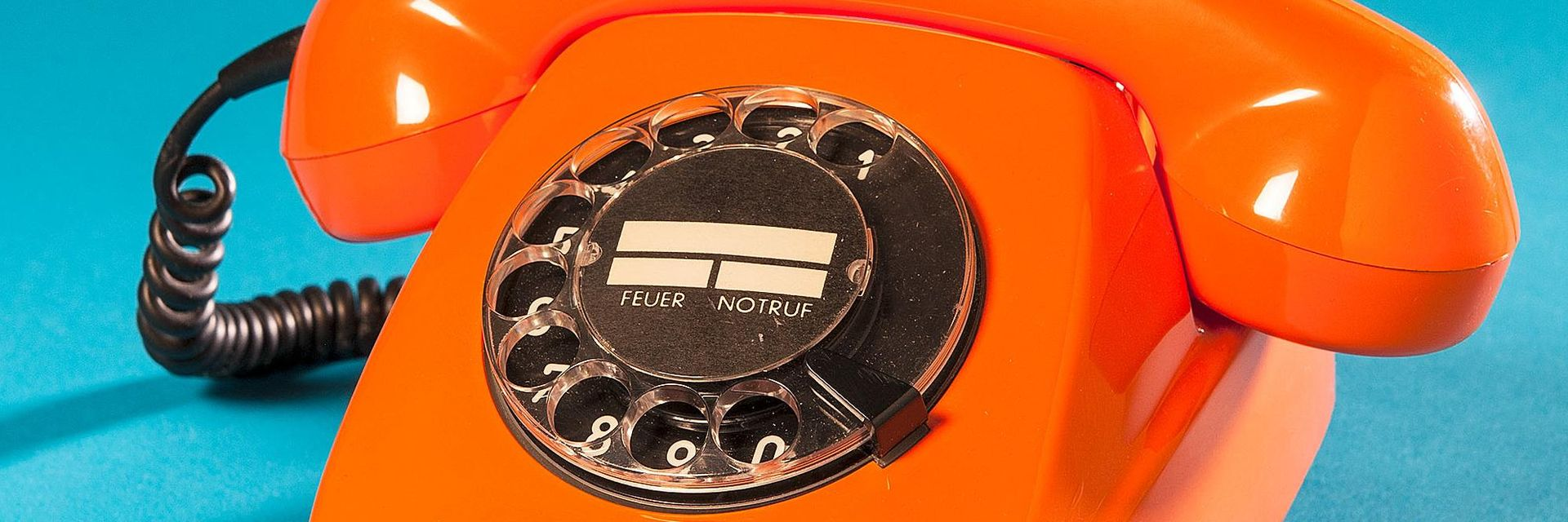 An orange corded telephone with a black rotary dial.