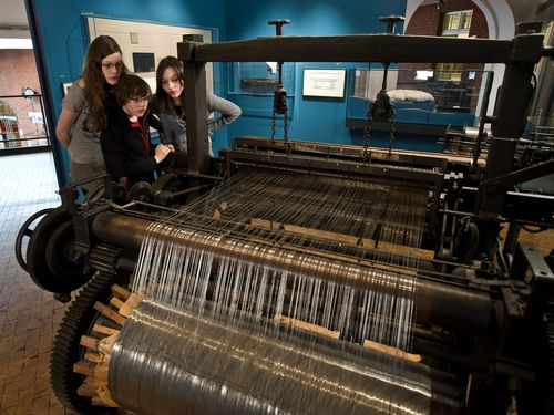 Three children look at a large, historical wire weaving loom in the exhibition.